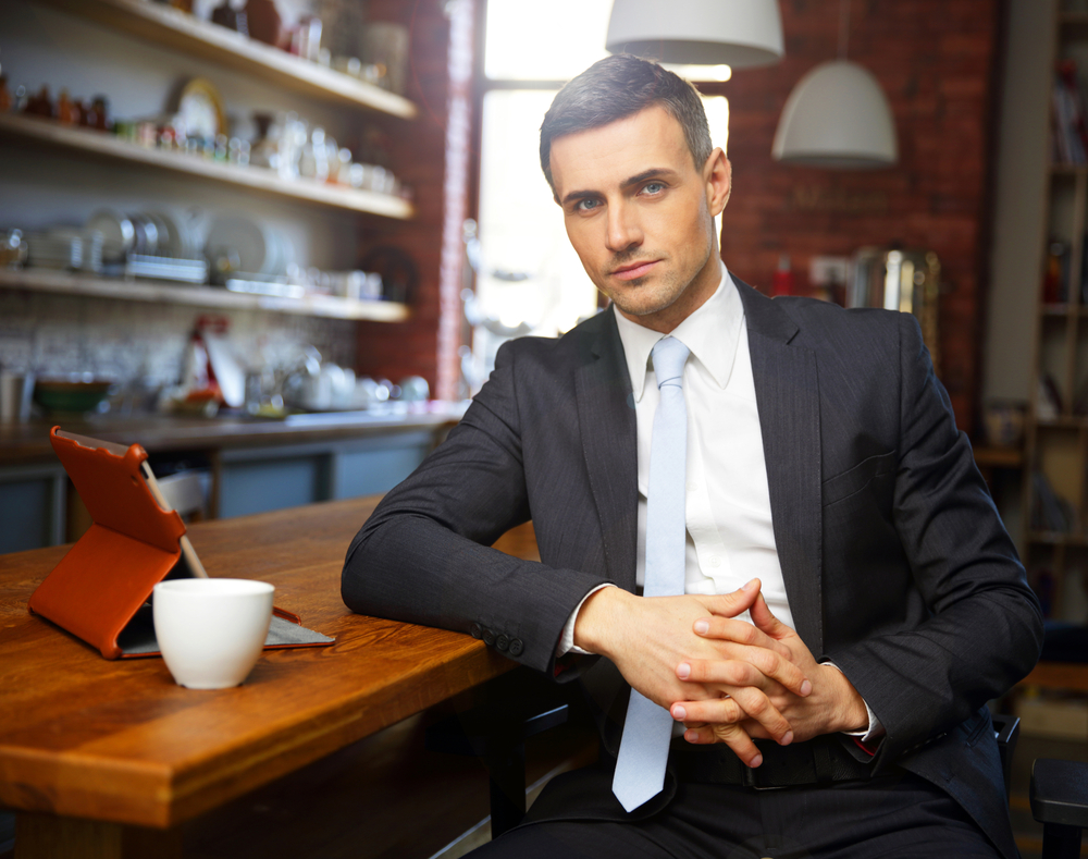 Confident businessman in formal cloths drinking coffee and reading news in the kitchen