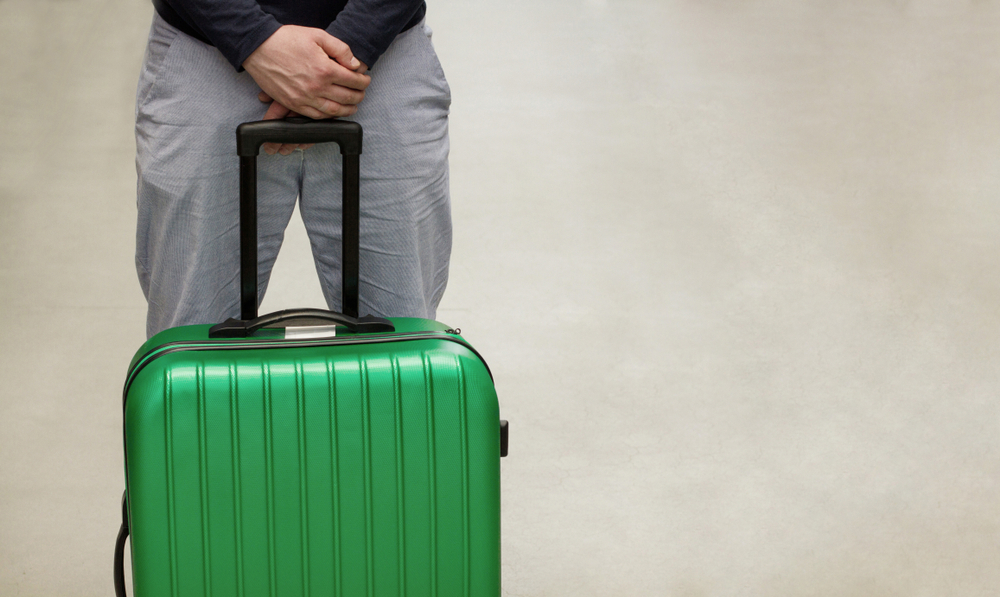 Man with suitcase waiting to leave
