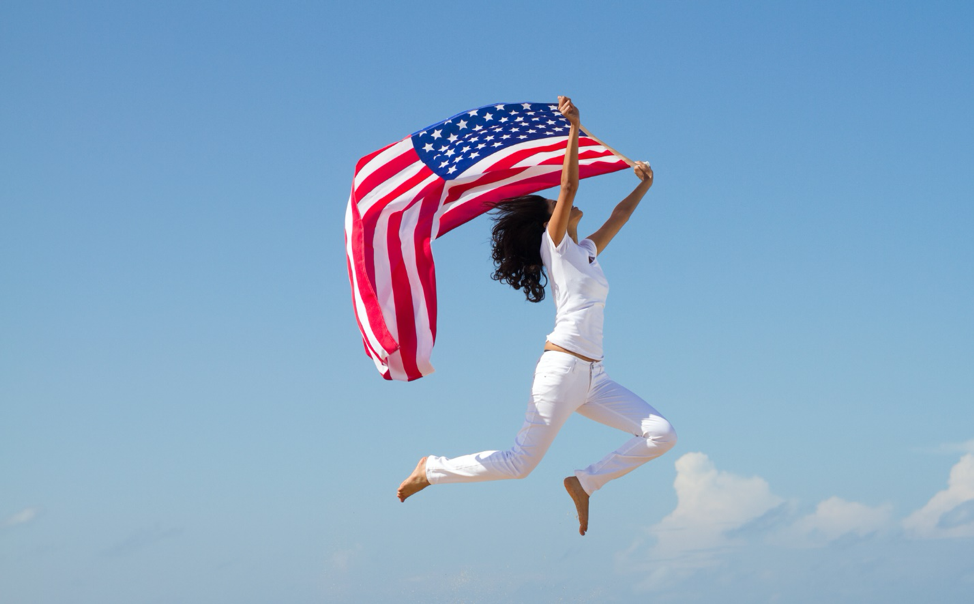 Woman jumping with the American flag